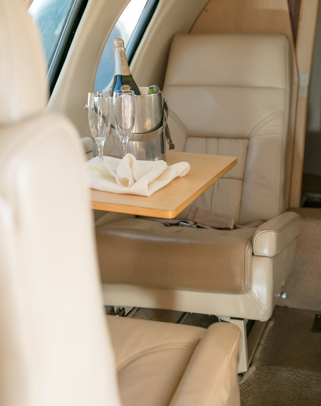 seats and table inside private jet with champagne bucket on table